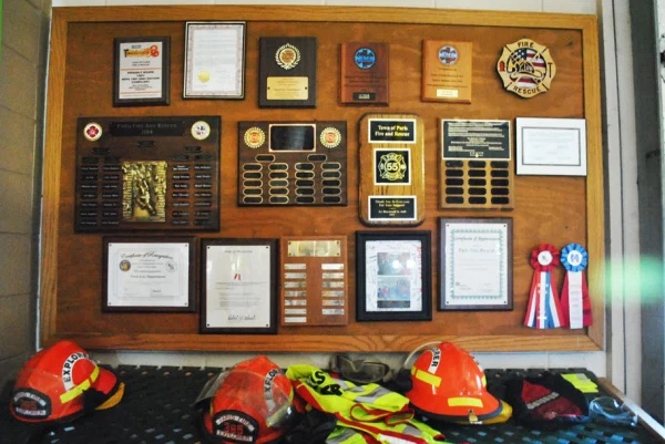 Bulletin board at fire station with plaques, ribbons, and fire helmets
