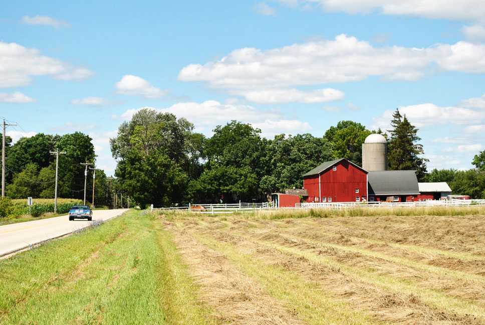 Field with red barn and blue car driving on a road